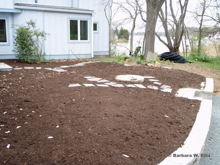 Before: Once the site was graded, a millstone unearthed on the property was set in place and the garden was mulched to protect the soil during the planting process. Informal stepping stone paths wind their way through the site.