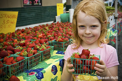 child with strawberries at farmer's market
