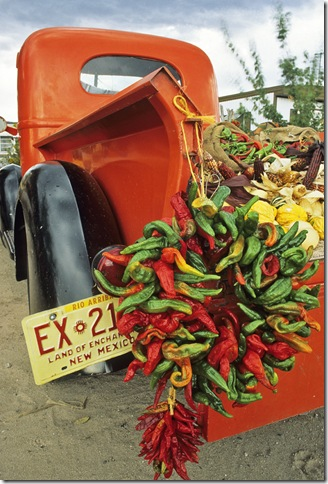A red pickup truck adorned with a chile ristra and loaded with bounty from the autumn harvest create a colorful scene at a fruit stand near the small village of Velarde in northern New Mexico.