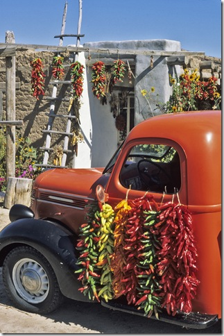 A red pickup truck draped with bright chile ristas makes a colorful composition in September at a fruit stand near the village of Velarde in northern New Mexico.