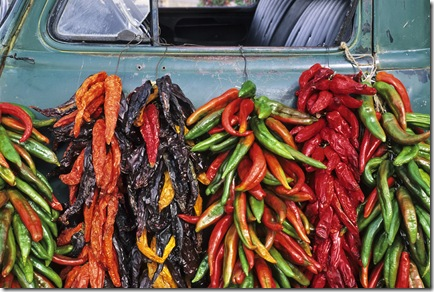In September, strings of red, orange and green chile peppers hang from an old pickup truck at a fruit stand near the village of Velarde in northern New Mexico.